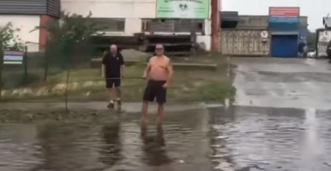Дождевые рыбаки: в Киеве мужчины ловили рыбу прямо на дороге